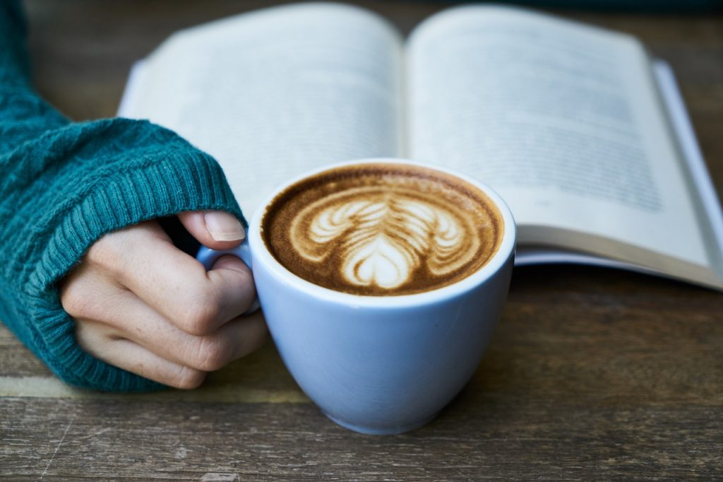 woman holding coffee and reading a book